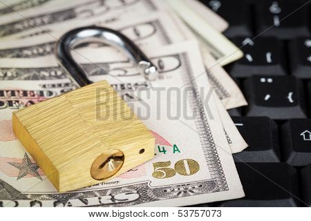 Open padlock and a stack of money on a black computer keyboard