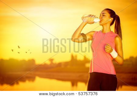 thirsty female jogger drinking water from bottle
