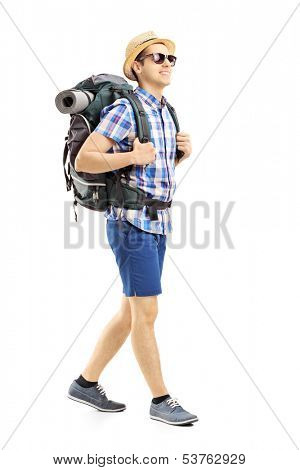 Full length portrait of a male hiker with backpack walking isolated on white background