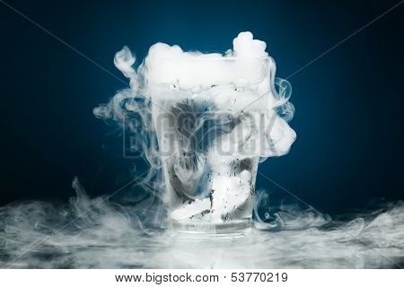 glass of water with ice vapor, blue background