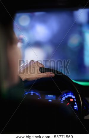 Over the shoulder view of businessman driving at night in city