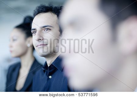 Young businessman sitting in business meeting with colleagues