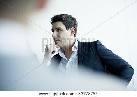 Young businessman listening in business meeting