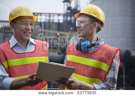 Two engineers in protective workwear standing and laughing outside of factory