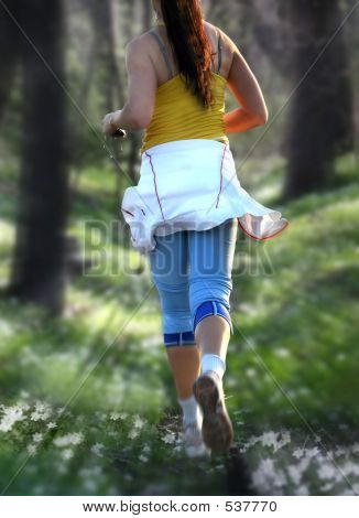 Young Woman Is Running Along The Forest