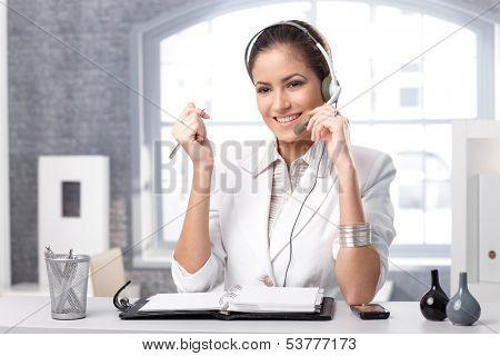 Smiling dispatcher working at office desk with headset, holding microphone.