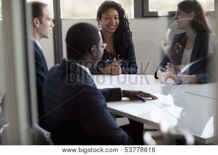 Four business people sitting and discussing at business meeting