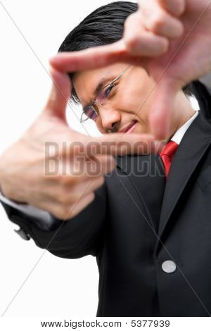 Asian Businessman Looking At His Perspetive By Framing His Fingers