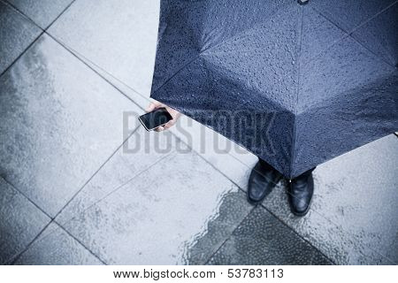 High angle view of businessman holding umbrella and looking at his phone in the rain