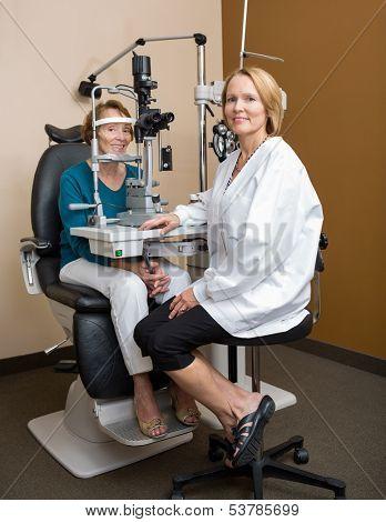Full length portrait of female optometrist examining senior patient's eyes with slit lamp in store