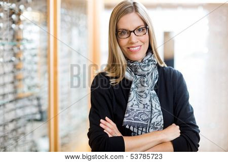 Portrait of beautiful woman wearing glasses with arms crossed in optician store
