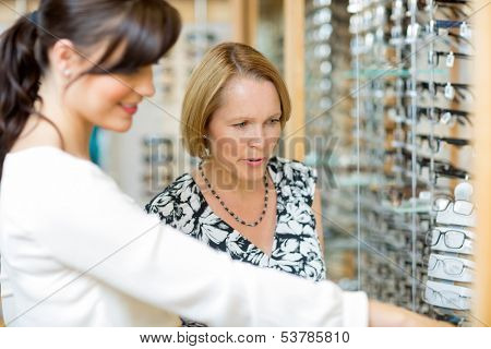 Salesgirl assisting senior woman in selecting glasses at optician store