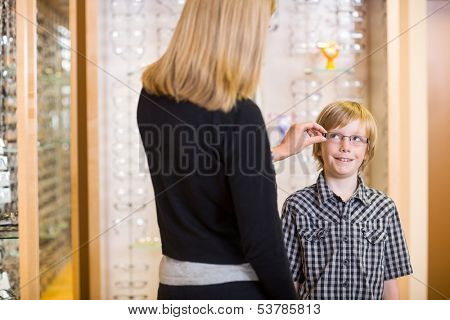Rear view of mother trying spectacles on preadolescent son at shop