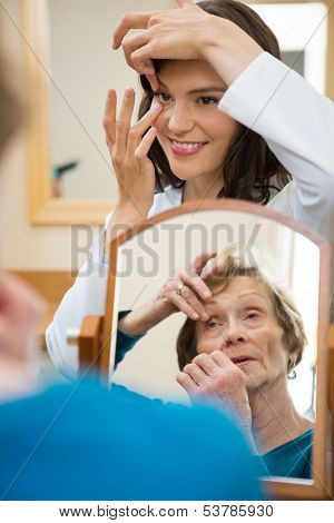 Female optometrist teaching senior woman to insert contact lens in optician store