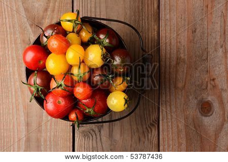 Baby Heirloom Tomatoes in a bucket on a rustic wooden table top. Horizontal format, looking down on the pail.