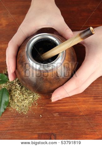 Woman hands holding calabash and bombilla with yerba mate on wooden background