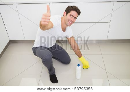 Portrait of a smiling young man cleaning the kitchen floor while gesturing thumbs up at house