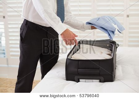 Side view mid section of a businessman unpacking luggage at a hotel bedroom