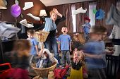 image of housekeeping  - A housewife is stressed and tried trying to clean the house while wild children are running around making a mess for a discipline or parenting concept - JPG