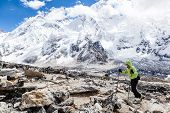 picture of avalanche  - Young woman hiker hiking in Himalaya Mountains in Nepal over Mount Everest and Nuptse face with snow and avalanches - JPG