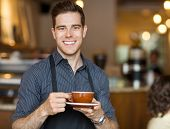 picture of waiter  - Portrait of happy waiter holding coffee cup while standing in cafeteria - JPG