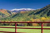 stock photo of cade  - Red fence enclosing a quiet pasture in Cade - JPG
