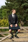 stock photo of kilt  - A young Scotsman in full kilt dress wear sitting on a gate - JPG