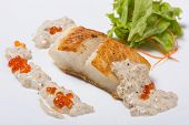 stock photo of halibut  - Fried halibut fillet with pepper sauce with salmon caviar and lettuce - JPG