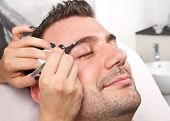 stock photo of eyebrow  - Beautician plucking a beautiful man eyebrows with tweezers in a beauty salon - JPG