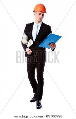 Confident businessman in helmet reading construction plan over white background