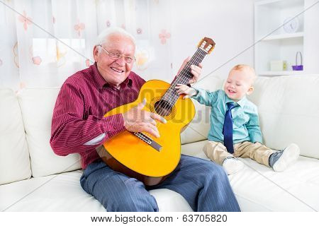Grandfather playing the guitar to his grandson