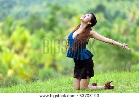 Beautiful stylish Filipina woman rejoicing in nature kneeling in the green grass in the countryside with her head back and arms outspread in the sunshine with a joyful smile