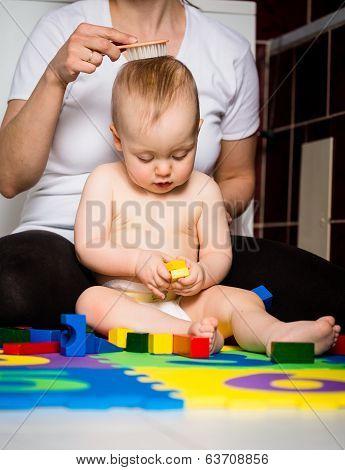 Mother brushing baby's hair