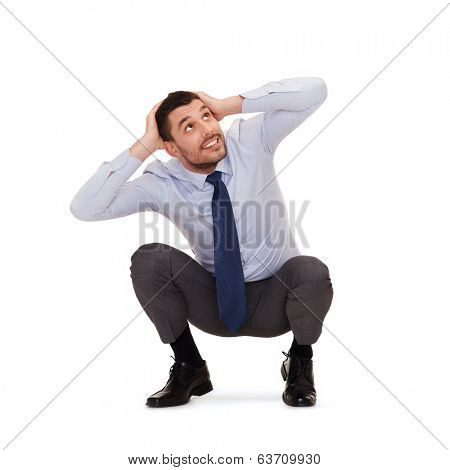business and education concept - smiling businessman crouching on the floor