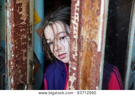 Little girl standing near an open window