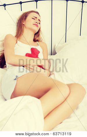 Beautiful caucasian woman lying in bed with hot water bag. Indoor background.