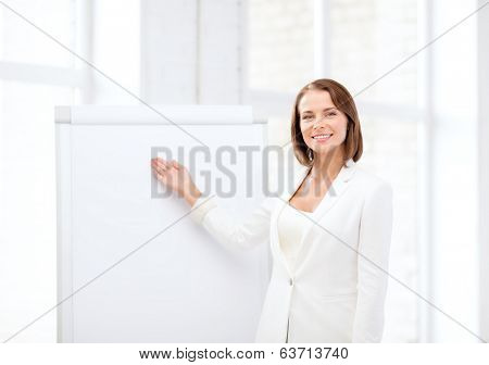 business and education concept - smiling businesswoman showing flipchart