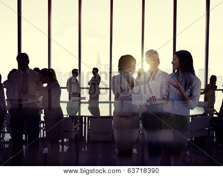 Silhouettes Of Multi-Ethnic Group Of Business People Working Together In A Board Room