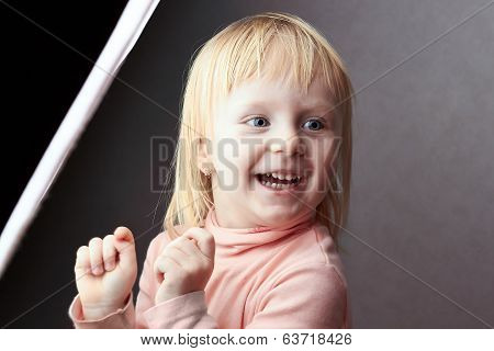 Small  Girl Stands Beside A Softbox