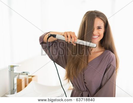 Happy Young Woman Straightening Hair In Bathroom