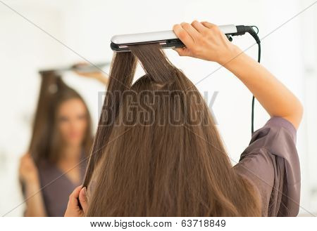 Young Woman Using Hair Straightener In Bathroom. Rear View