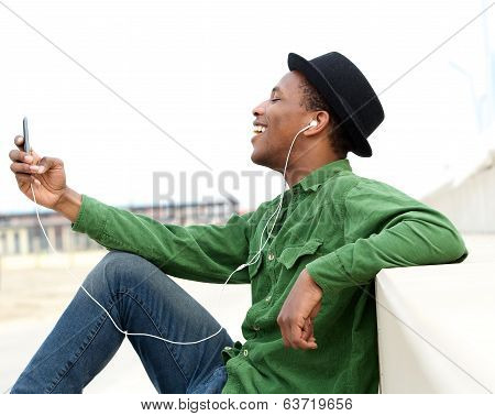 Young Man Listening To Music On Cellphone