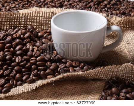 white cup with coffee on burlap background with beans
