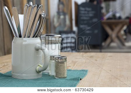 Cutlery in a beer mug on a beer garden table