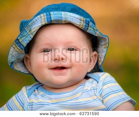 Outdoor portrait of happy smiling infant baby boy
