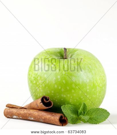 Granny Smith green apple with cinnamon and mint on a white background