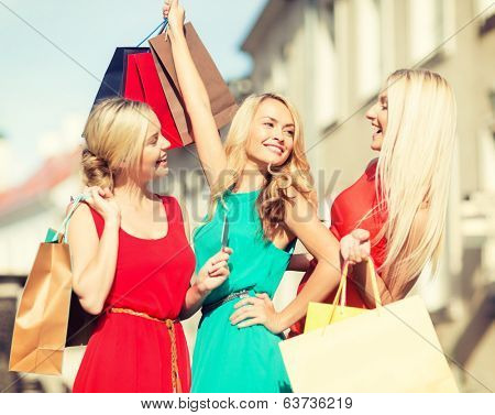 sale and tourism, happy people concept - beautiful blonde women with shopping bags in the ctiy