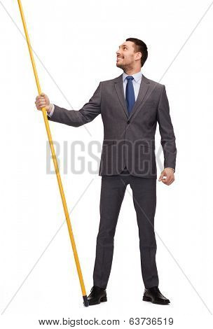 business and advertisement concept - smiling businessman holding flagpole with imaginary flag