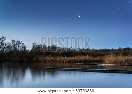 Calm Tranquil Moonlit Landscape Over Lake And Jetty