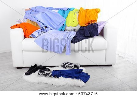 Messy colorful male clothing on  sofa on light background